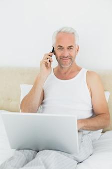 Hombre maduro sonriente que usa el teléfono móvil y la computadora portátil en cama