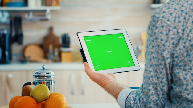 Hombre maduro con tablet pc con chroma key en la cocina durante el desayuno. anciano con maqueta de maqueta aislada de pantalla verde para un fácil reemplazo