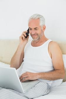 Hombre maduro con teléfono móvil y portátil en la cama
