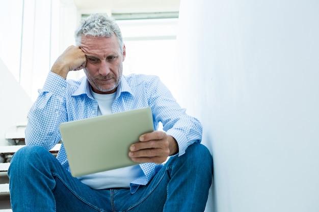 Hombre maduro tensado que sostiene la tableta mientras está sentado en pasos