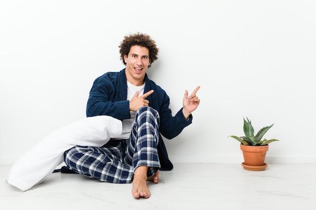 Hombre maduro vistiendo pijama sentado en el piso de la casa apuntando con los dedos índices