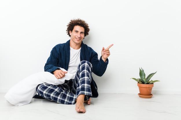 Hombre maduro vistiendo pijama sentado en el piso de la casa emocionado señalando con los dedos lejos.