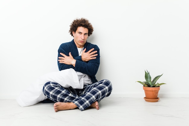 Hombre maduro vistiendo pijama sentado en el piso de la casa se enfría debido a la baja temperatura o una enfermedad.
