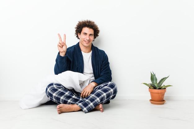 Hombre maduro vistiendo pijama sentado en el piso de la casa mostrando el número dos con los dedos.