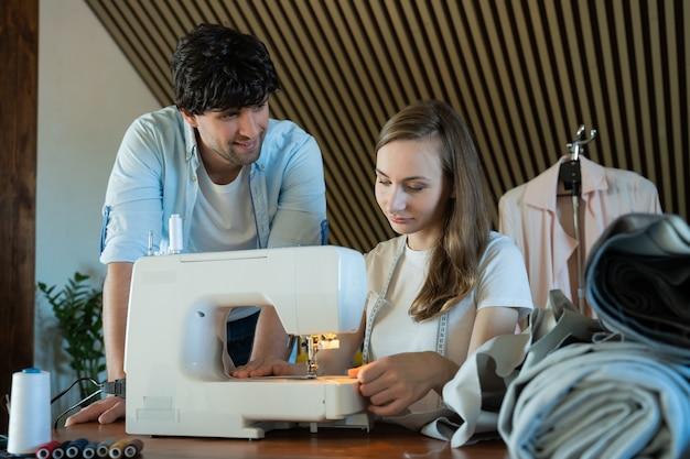 Hombre maestro ayudando a una mujer estudiante de moda a aprender a usar la máquina de coser