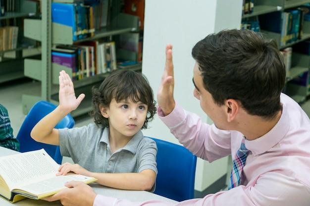 Hombre maestro y niño estudiante aprenden con el libro en la estantería