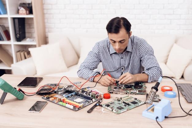 Hombre maestro reparando electrodomésticos en la mesa en casa.