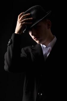 Hombre mafioso guapo tocar el sombrero en la oscuridad