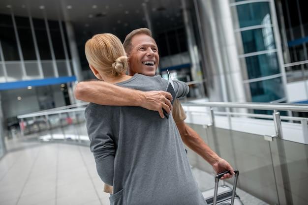 Hombre con maleta abrazando a mujer rubia