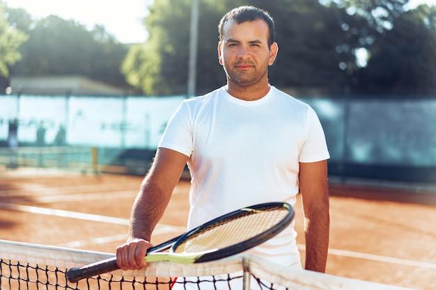 Hombre manchado con raqueta de tenis de pie en la cancha de arcilla cerca de la red