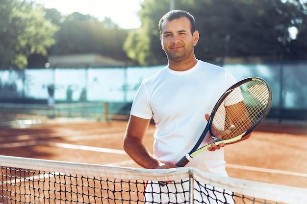 Hombre manchado con raqueta de tenis de pie en la cancha de tenis de arcilla cerca de la red
