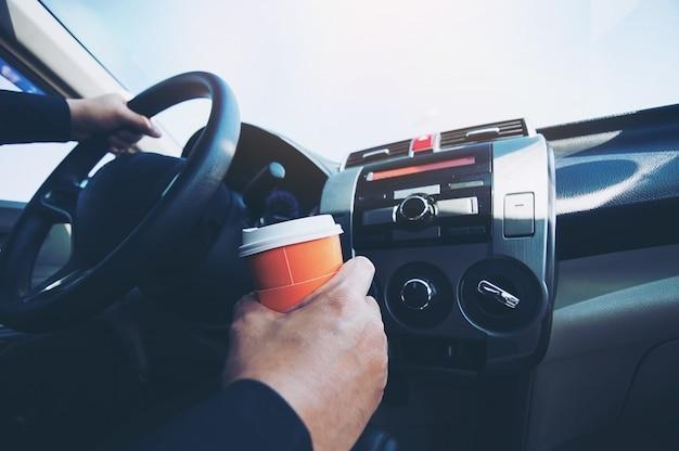 El hombre maneja el auto mientras sostiene una taza de café caliente: conducción de automóviles con sueño o concepto dormido