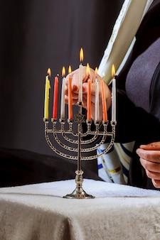Hombre mano encendiendo velas en menorá en la mesa servida para hanukka