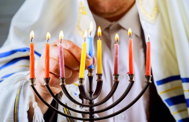 Hombre mano encendiendo velas en menorá sobre la mesa hanukkah