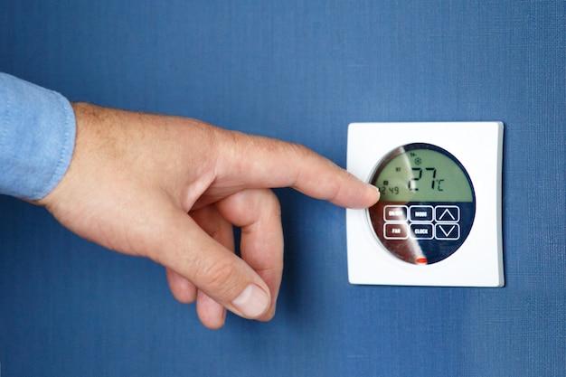 Hombre mano encienda el interruptor remoto de aire acondicionado.