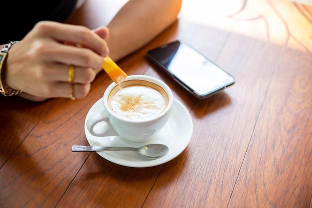 Hombre mano poniendo azúcar en la taza de café