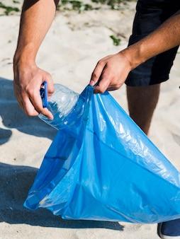 Hombre mano poniendo una botella de plástico transparente en una bolsa de basura azul