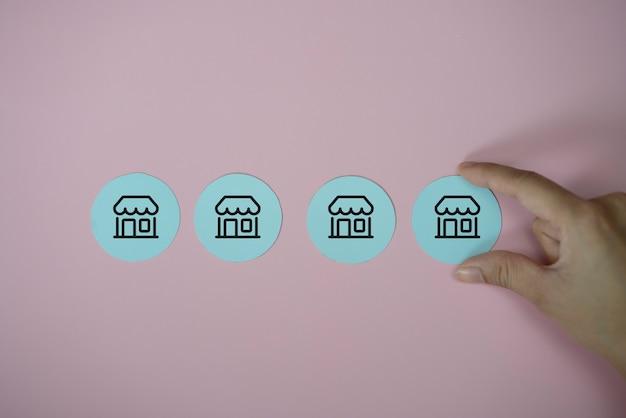 El hombre de la mano del primer elija el corte del papel del icono con el sistema de la comercialización de la franquicia en fondo azul