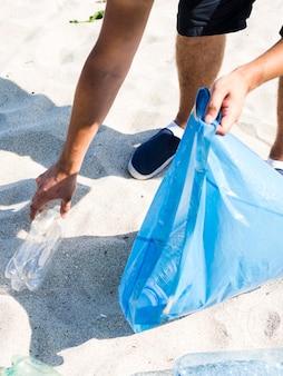 Hombre mano recogiendo botellas de plástico mientras sostiene la bolsa de basura azul en la playa
