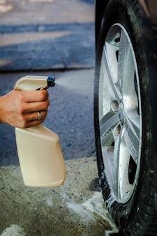 Hombre mano rociando una rueda de coche