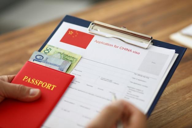 Hombre mano sostenga la pluma de plata con pasaporte.