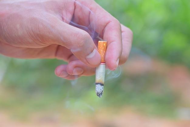 Hombre mano sosteniendo un cigarrillo para fumar cerca