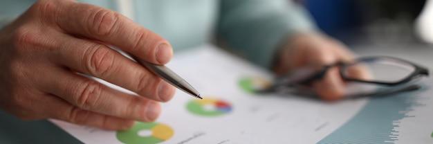 Hombre mano sosteniendo papel con estadísticas financieras