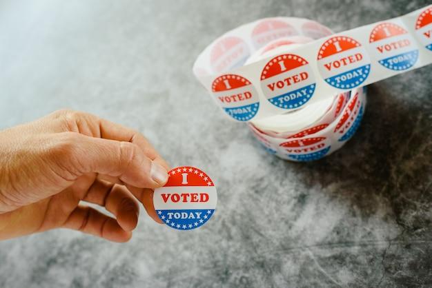 Hombre mano sosteniendo pegatinas de partidario de las elecciones americanas
