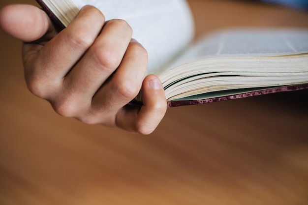 Hombre mano sostiene el libro abierto. vista del primer plano del libro.