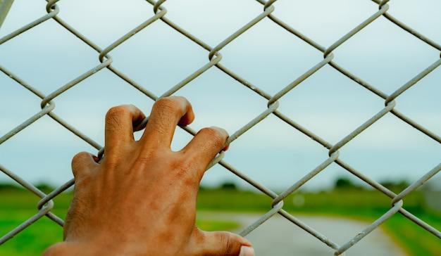 Hombre mano sujetando una valla metálica para refugiados e inmigrantes concepto de angustia de vida y libertad