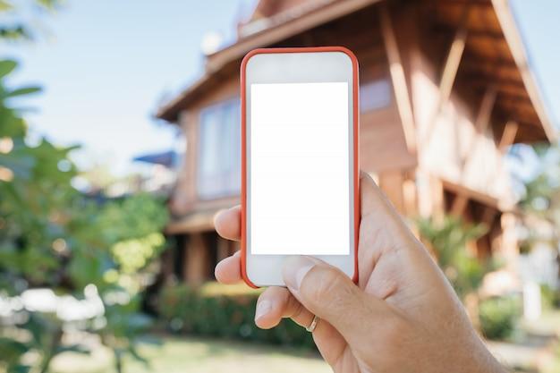 Hombre mano teléfono blanco en casa de verano. inversiones y una aplicación para elegir bienes inmuebles.