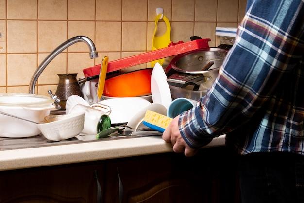 Hombre de la mano con una toallita cerca de muchos platos sucios en el fregadero de la cocina que desea lavar