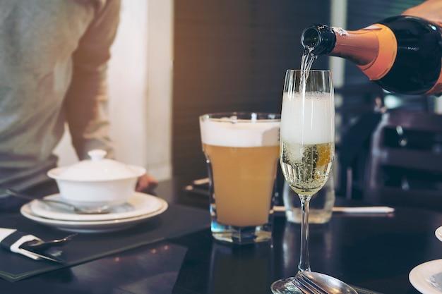 Hombre mano vertiendo champán en vaso listo para beber sobre borrosa mesa en restaurante