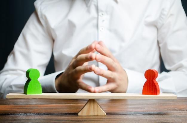 Un hombre con las manos en la cerradura y mira a las figuras rojas y verdes rivales en una balanza.