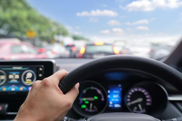 Hombre manos conductor en el volante de un coche moderno