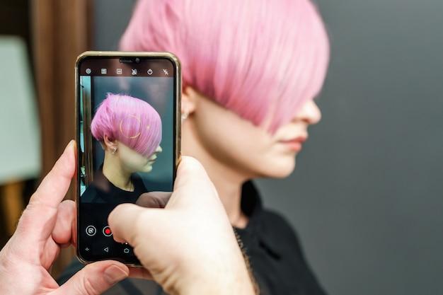 Hombre manos hace foto un peinado rosa en pared gris