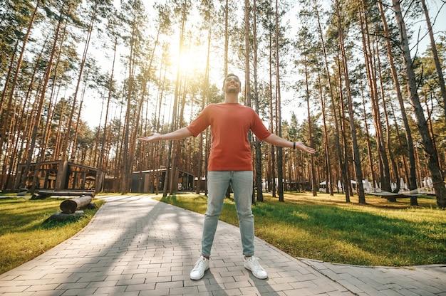 Hombre con las manos a los lados de pie al sol