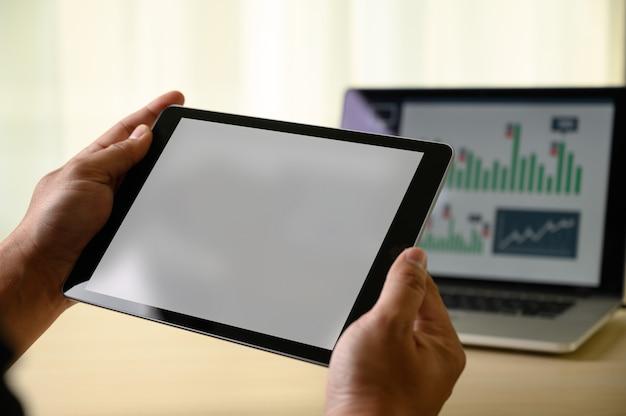 Hombre manos multitarea hombre usando tableta cerca hasta cerrar trabajando en la oficina