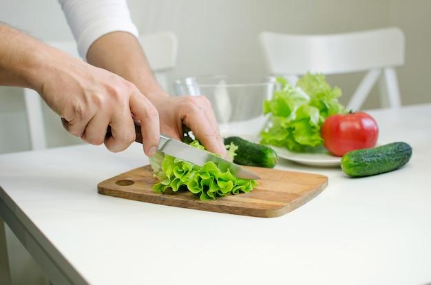 Hombre manos prepairing ensalada. corte de salat.