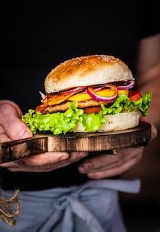 Hombre manos sosteniendo una jugosa sabrosa hamburguesa con carne de res, lechuga, pepinillos, tomate y aros de cebolla en una mesa de madera. comida callejera clásica - hamburguesa a la parrilla