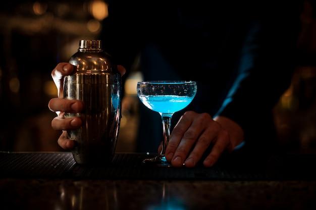 Hombre manos sosteniendo un vaso con cóctel y botella de verano azul