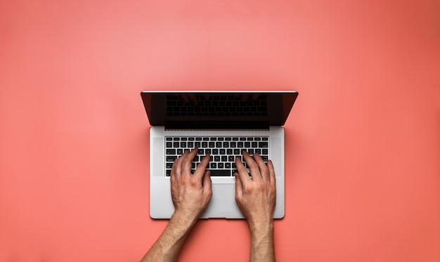 Hombre manos usando laptop en escritorio rosa