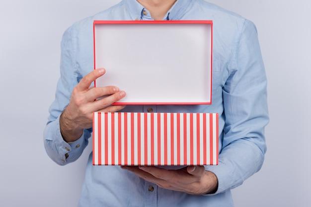 El hombre mantiene abierta la caja festiva. caja de regalo en manos de hombres. vista frontal.