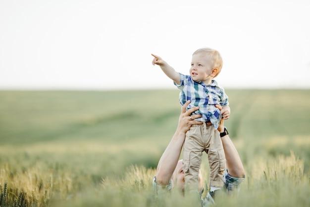 El hombre mantiene al niño sobre su cabeza entre el campo