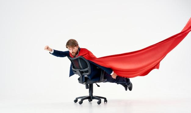 Hombre con manto rojo en el estudio de superhéroes de gerente de silla de oficina. foto de alta calidad