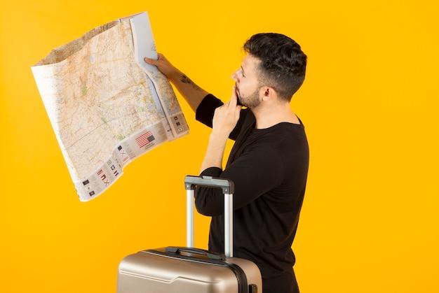 Hombre con un mapa y un concepto de viaje de maleta, está perdido