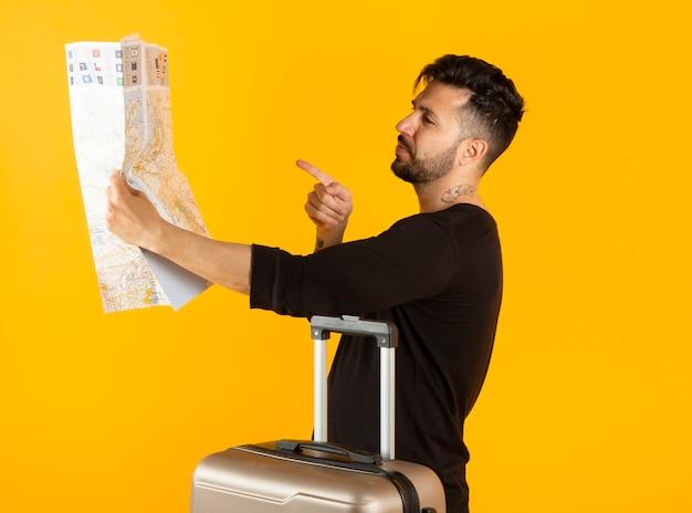 Hombre con un mapa y una maleta viajando concepto