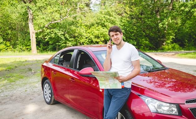 Hombre con el mapa en la mano de pie junto a un coche en el bosque
