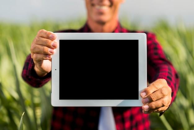 Hombre de maqueta sosteniendo una tableta en un campo