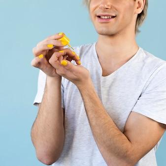 Hombre de maquillaje con esmalte de uñas rojo
